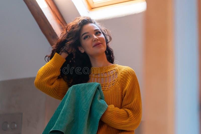 Jovem morena atraente em camisola amarela secando cabelo crespo com toalha azul Método curly de cuidado capilar foto de stock royalty free