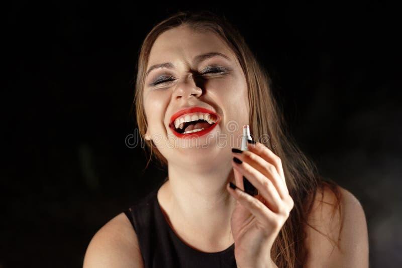Jovem morena vaporizando e-cigarro com fumaça sobre fundo escuro, rindo, bêbada Batom vermelho, olhos fumegantes, manicure preta, imagens de stock royalty free
