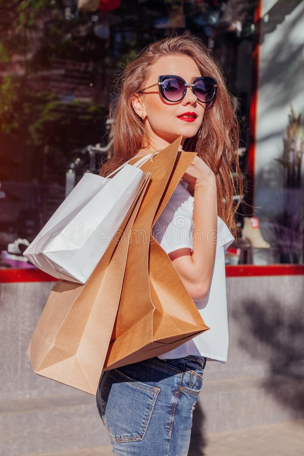 Jovem mulher à moda bonita que anda com os sacos de compras na rua da cidade ao longo das mostras e das lojas Enegreça sexta-feir imagens de stock