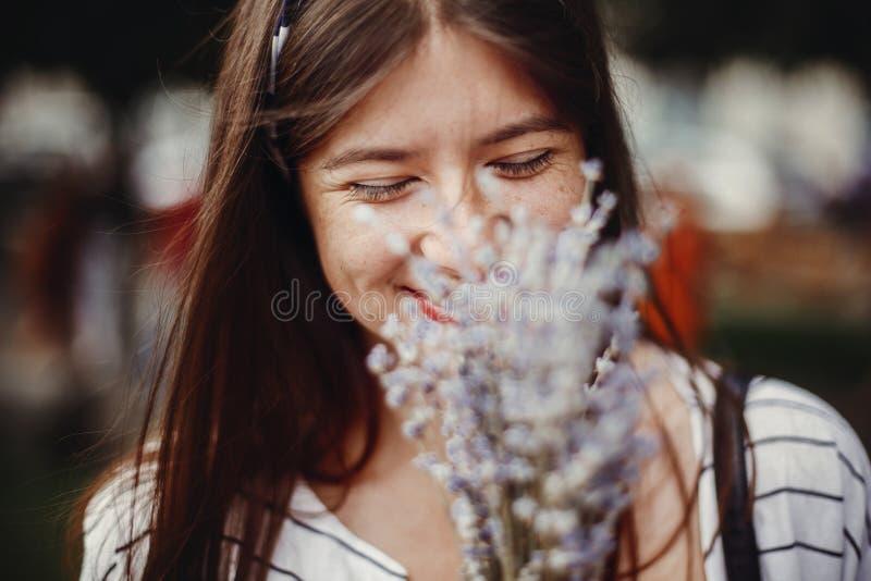 Jovem mulher à moda bonita que guarda as flores de surpresa a da alfazema foto de stock royalty free