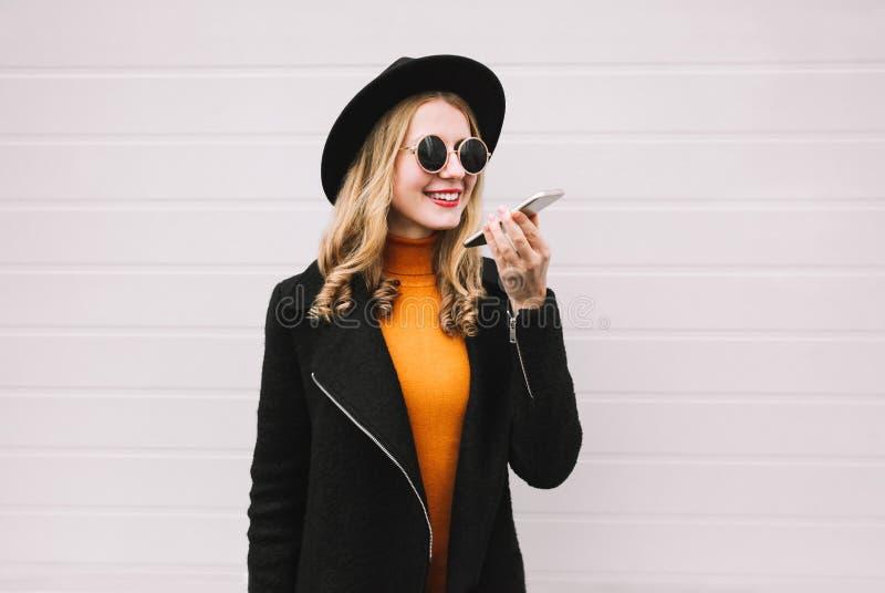 Jovem mulher à moda com smartphone usando o registrador ou a chamada do comando da voz fotografia de stock