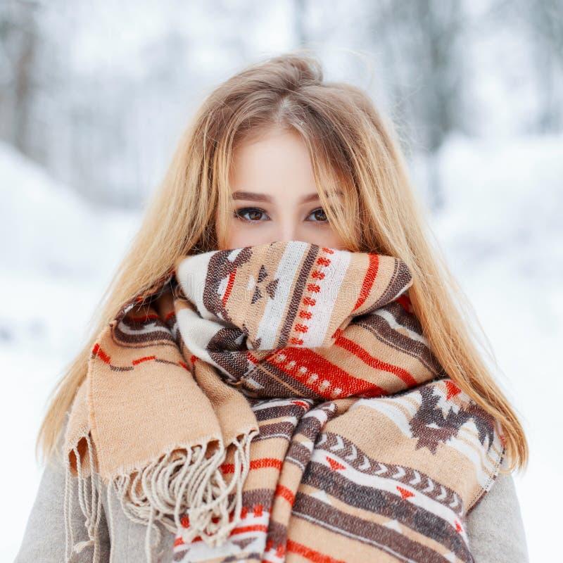 Jovem mulher à moda de encantamento com olhos marrons em um revestimento cinzento elegante do vintage em mitenes mornos em um par imagens de stock