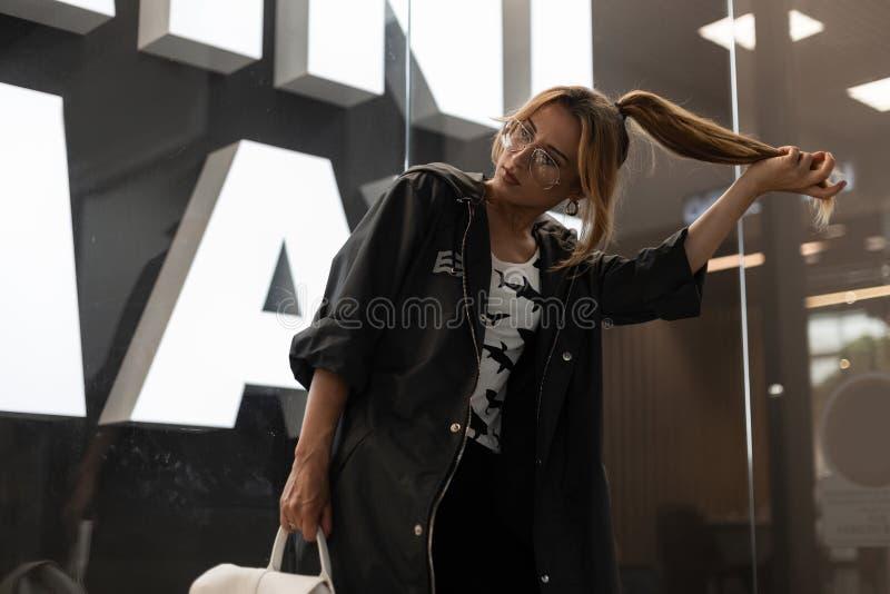 Jovem mulher à moda em vidros na moda em uma capa de chuva do vintage do verão em um t-shirt elegante com um teste padrão fotos de stock