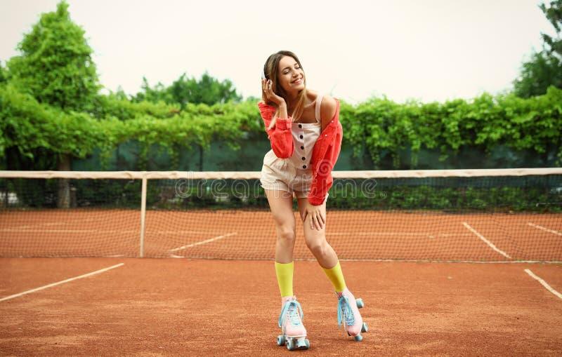 Jovem mulher à moda feliz com os patins de rolo do vintage no campo de tênis imagem de stock royalty free