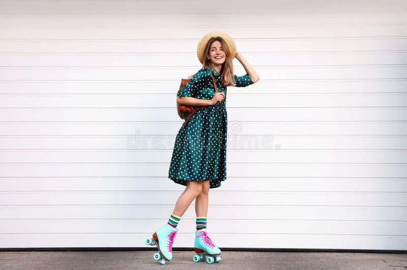 Jovem mulher à moda feliz com os patins de rolo do vintage, o chapéu e a trouxa perto da porta branca da garagem imagem de stock