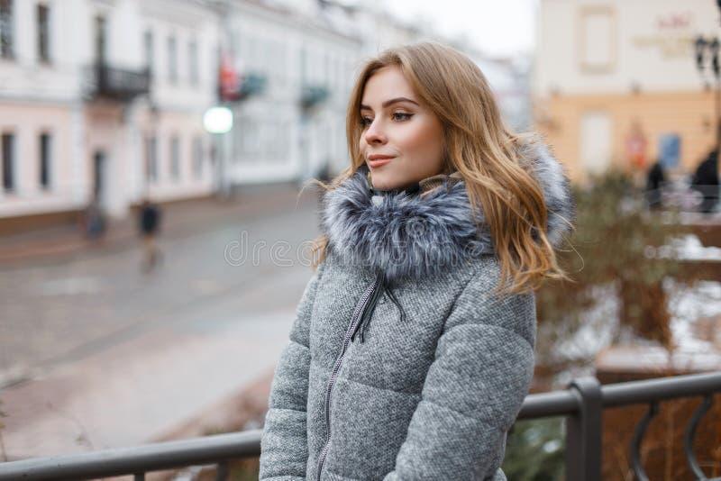 Jovem mulher à moda feliz em um chapéu feito malha cinzento em um revestimento elegante do inverno com pele em mitenes mornos fei foto de stock royalty free