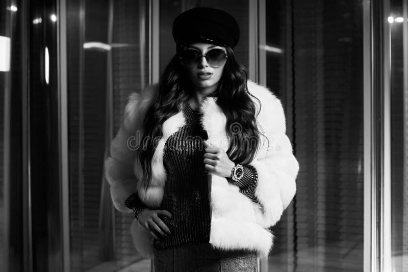 Jovem mulher à moda no casaco de pele branco e em óculos de sol redondos fotografia de stock
