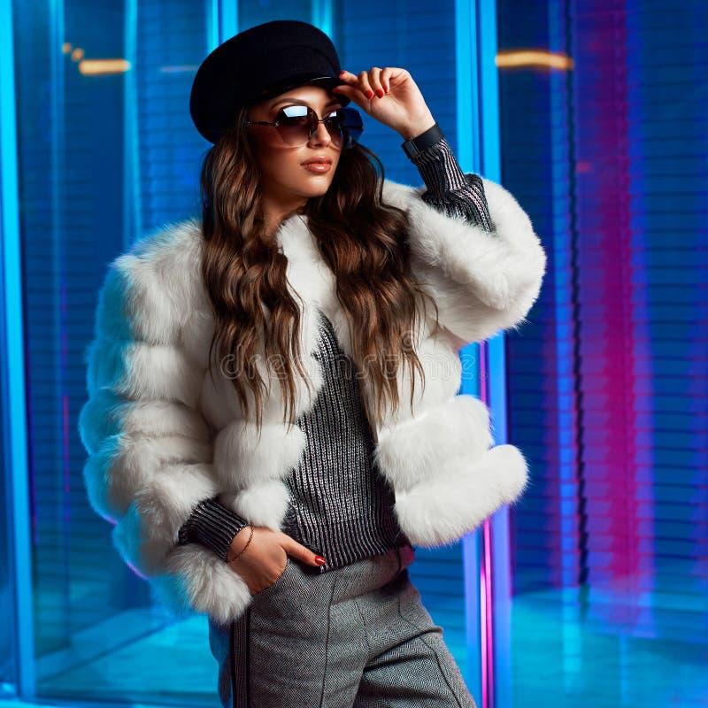 Jovem mulher à moda no casaco de pele branco e em óculos de sol redondos fotografia de stock royalty free