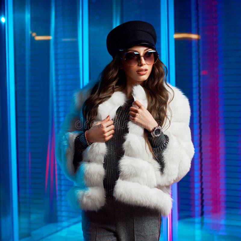 Jovem mulher à moda no casaco de pele branco e em óculos de sol redondos imagem de stock royalty free