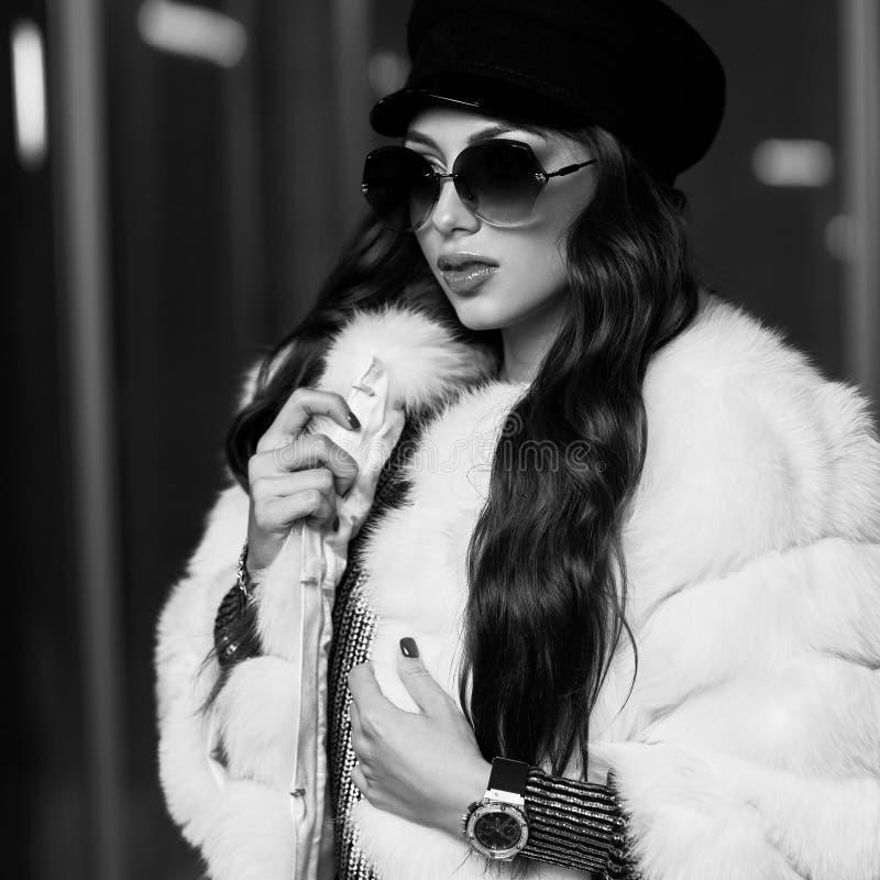 Jovem mulher à moda no casaco de pele branco e em óculos de sol redondos imagens de stock