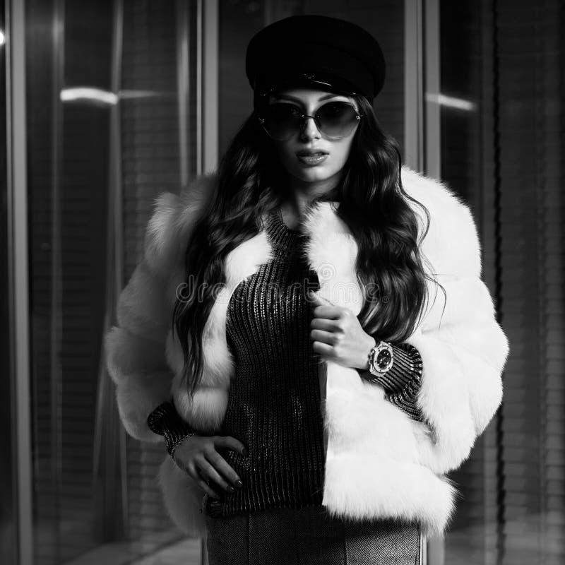 Jovem mulher à moda no casaco de pele branco e em óculos de sol redondos foto de stock