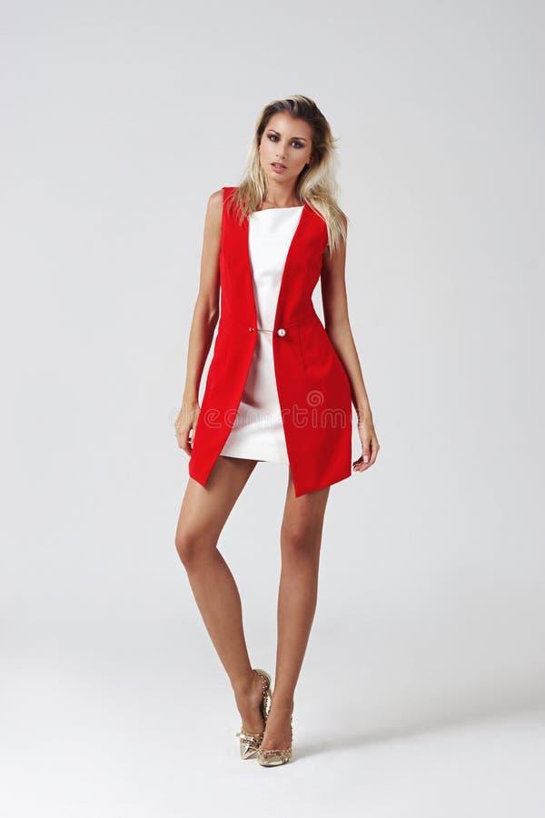 Jovem mulher à moda no vestido branco e no revestimento vermelho imagem de stock