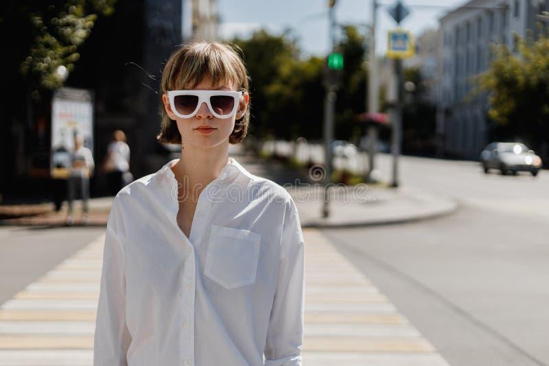 A jovem mulher à moda nos óculos de sol brancos vestidos na camisa branca está estando na rua da cidade em um dia ensolarado do v imagens de stock