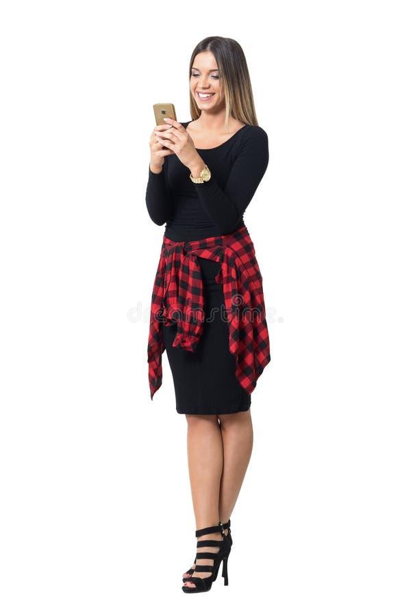 Jovem mulher à moda ocasional nos saltos altos e no riso preto da mensagem de telefone da leitura do vestido imagem de stock royalty free
