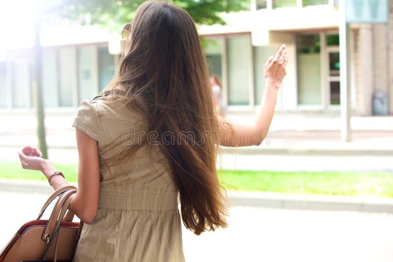 Jovem mulher à moda que acena para um táxi imagem de stock