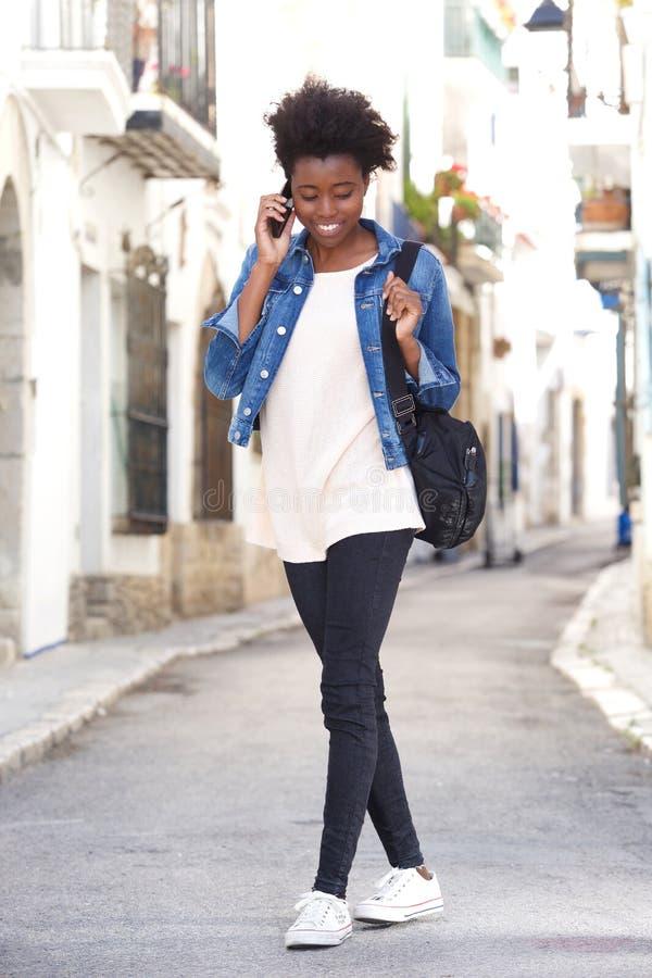 Jovem mulher à moda que anda abaixo da rua com telefone esperto fotografia de stock royalty free