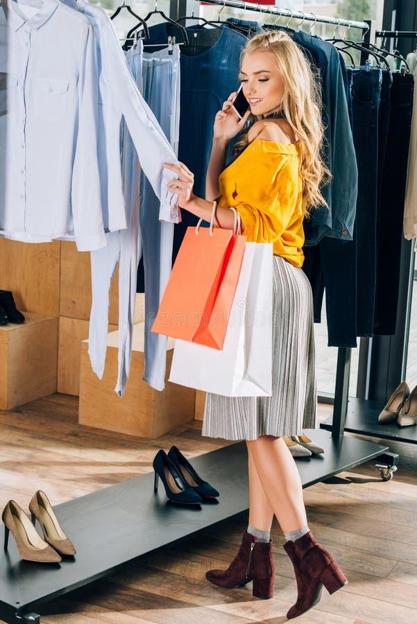 jovem mulher à moda que fala pelo telefone e que procura a roupa nova imagens de stock