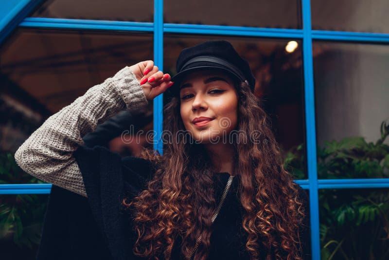 Jovem mulher à moda que levanta contra a janela azul fora Equipamento elegante Smiling modelo bonito foto de stock