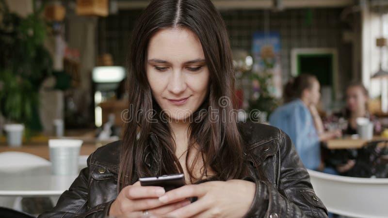 A jovem mulher à moda usa um smartphone envia os sms que sentam-se em uma tabela no café moderno, sorrindo 4K foto de stock