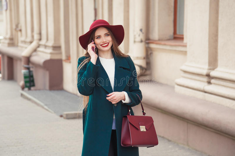 Jovem mulher à moda vestida bonita que sorri ao falar no telefone fora foto de stock royalty free