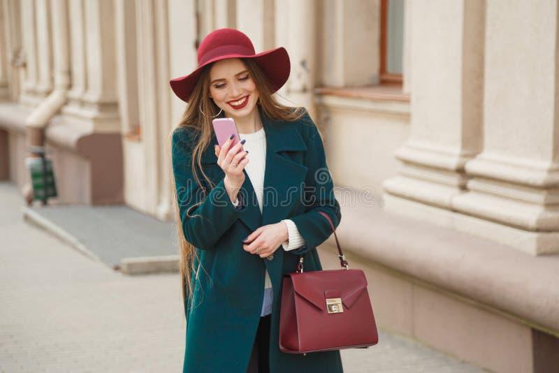 A jovem mulher à moda vestida bonita recebe um telefonema fotos de stock