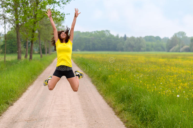 Jovem mulher ágil energética que pula para a alegria imagens de stock