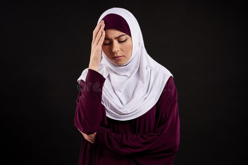 A jovem mulher árabe no hijab tem a dor de cabeça imagens de stock royalty free