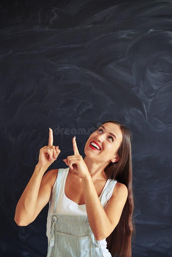 A jovem mulher é apontando e de vista dois dedos acima imagem de stock royalty free