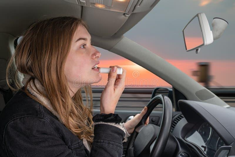 A jovem mulher é confundida ao conduzir e olha no morror de condução imagem de stock royalty free