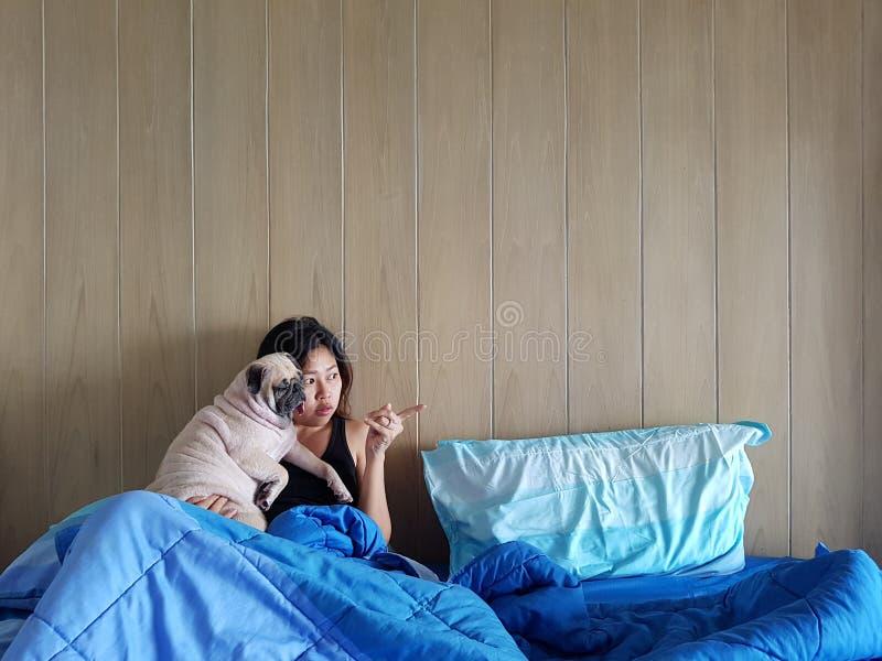 A jovem mulher é de encontro e de sono com o cão do pug na cama fotografia de stock royalty free