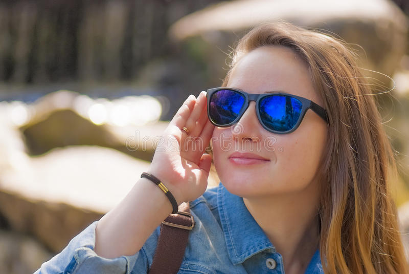 A jovem mulher, óculos de sol, menospreza o sorriso foto de stock royalty free