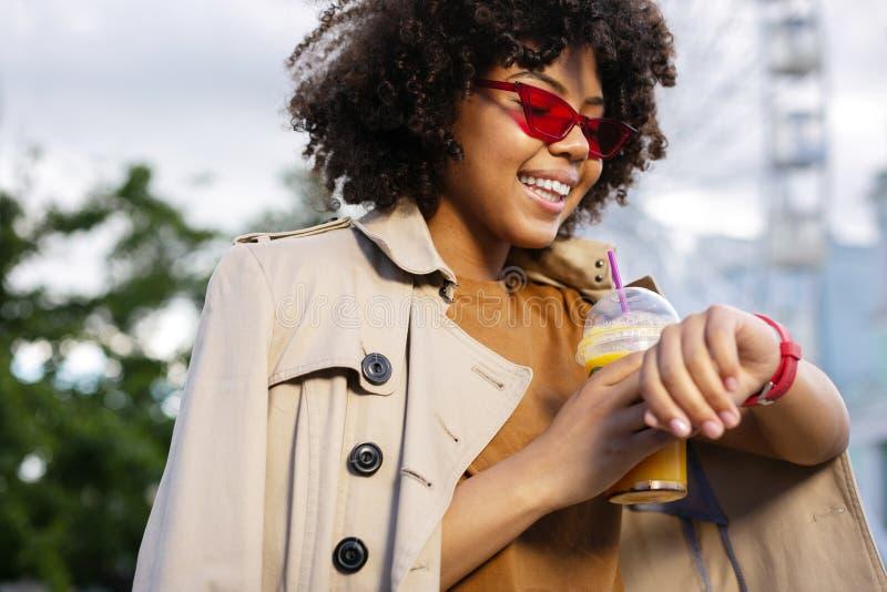 Jovem mulher adorável que verifica o tempo e que guarda o copo do suco imagens de stock royalty free