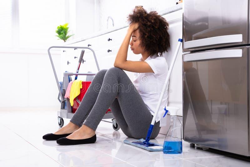 Jovem mulher africana cansado que senta-se na cozinha foto de stock