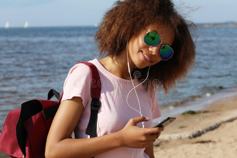 Jovem mulher afro-americana surpreendente encantador nos óculos de sol que escuta a música nos fones de ouvido em seu telefone ce fotos de stock