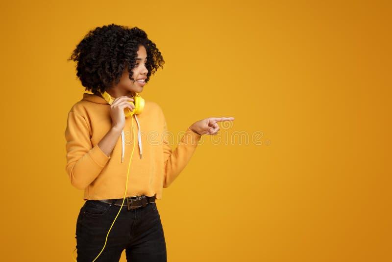 Jovem mulher afro-americano bonita com sorriso brilhante vestida na roupa ocasional e na roupa dos fones de ouvido que aponta o d imagens de stock