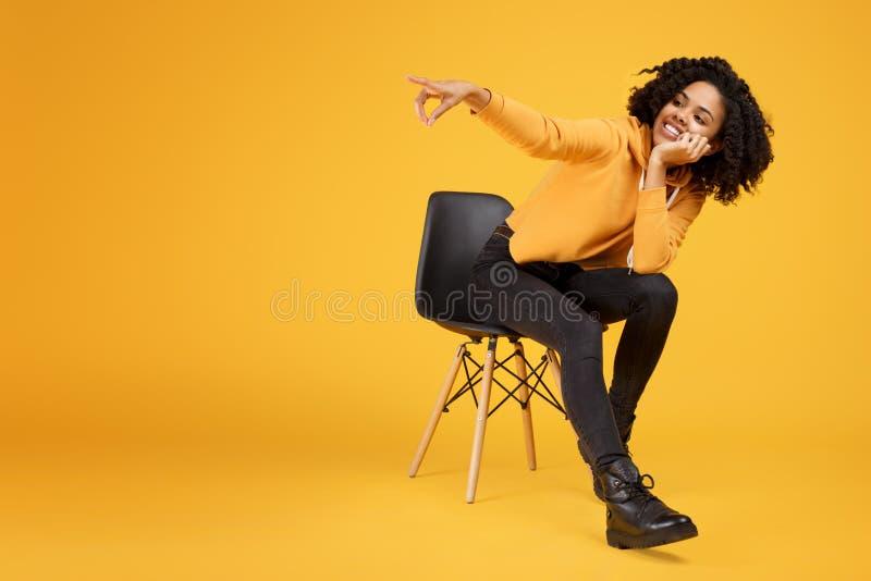 Jovem mulher afro-americano de encantamento com sorriso bonito vestida na roupa ocasional que senta-se na cadeira à moda e fotos de stock royalty free