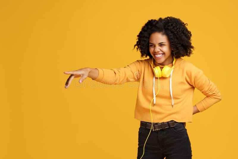 Jovem mulher afro-americano de encantamento com sorriso brilhante vestida em apontar da roupa da roupa ocasional e dos fones de o foto de stock royalty free