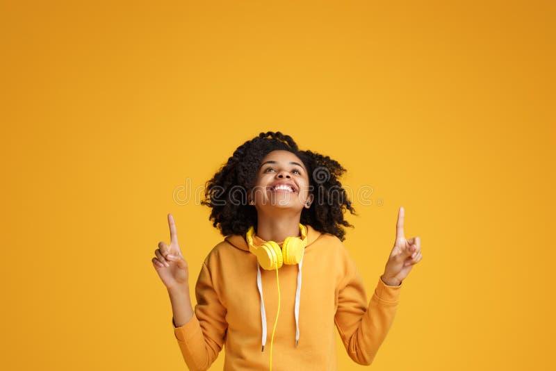 Jovem mulher afro-americano de encantamento com sorriso brilhante vestida em apontar da roupa da roupa ocasional e dos fones de o imagens de stock royalty free