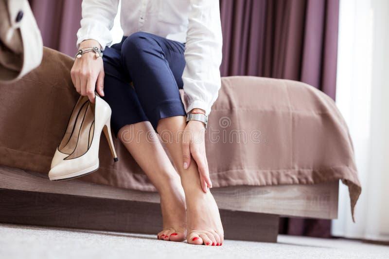 Jovem mulher agradável bonita que toca em seus pés foto de stock
