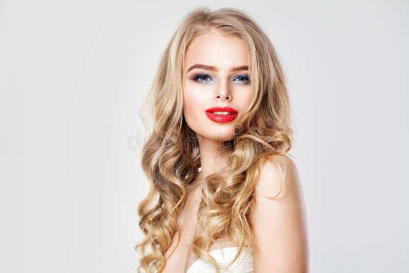 Jovem mulher agradável com composição e cabelo ondulado louro fotos de stock royalty free