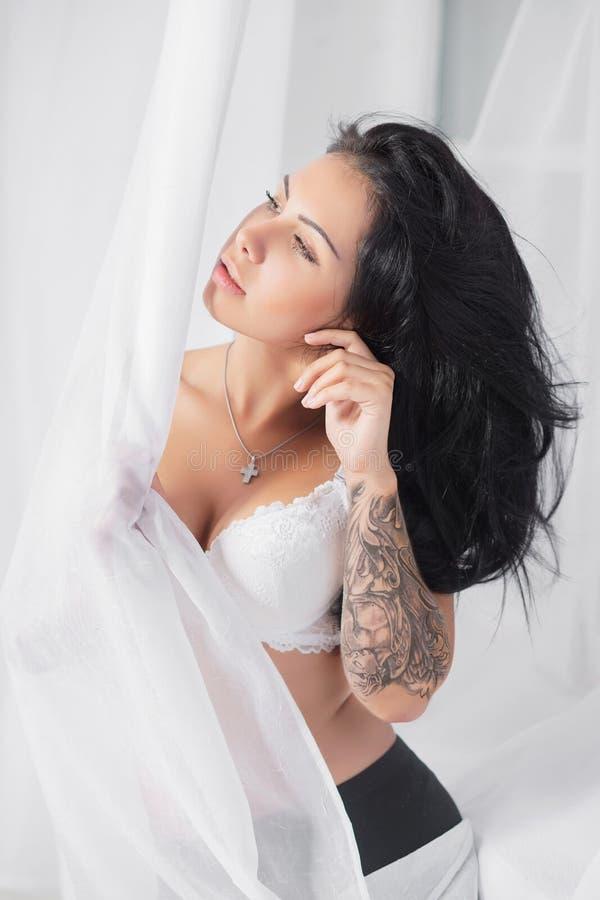 Jovem mulher agradável com a tatuagem que levanta no estúdio fotos de stock