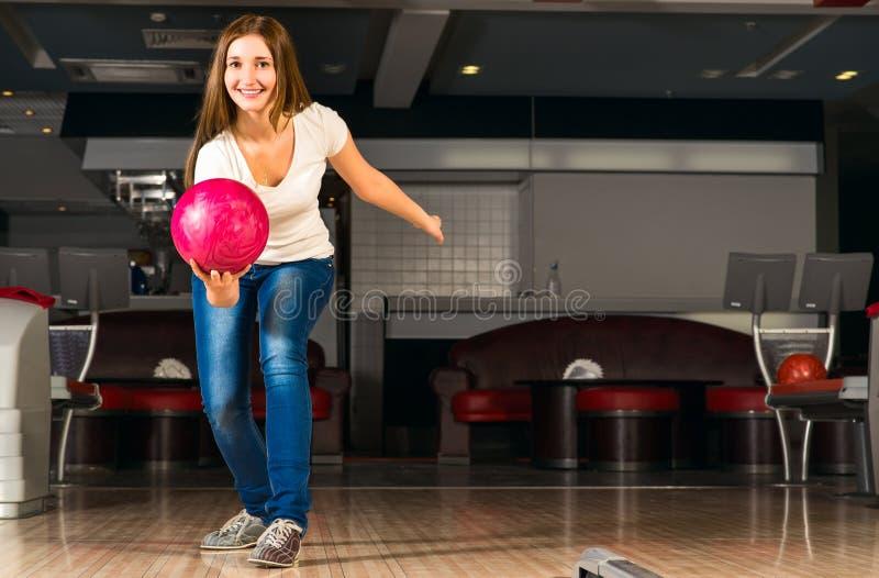 A jovem mulher agradável joga uma bola de boliches fotos de stock