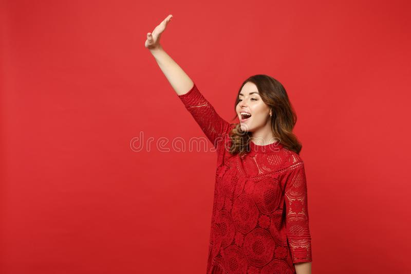 A jovem mulher agradável no vestido do laço que olha de lado, acenando e cumprimentando com mão como observações alguém isolou-se fotografia de stock