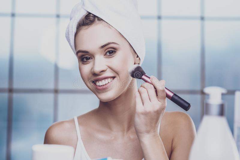 Jovem mulher agradável que aplica cosméticos imagens de stock