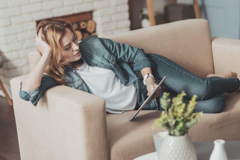 Jovem mulher agradável que lê o livro eletrônico imagens de stock royalty free