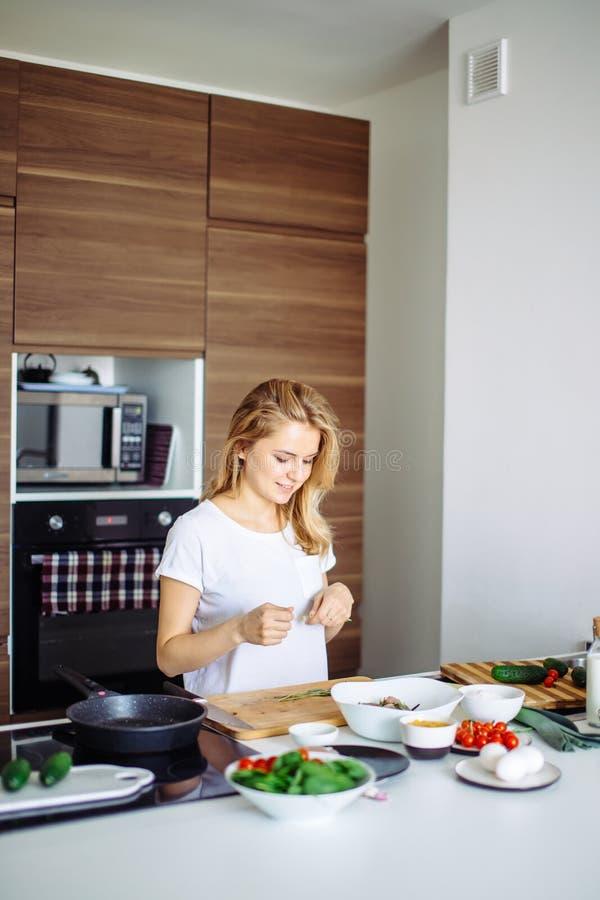 Jovem mulher agradável que prepara o jantar em um cozimento do conceito da cozinha, culinário foto de stock royalty free