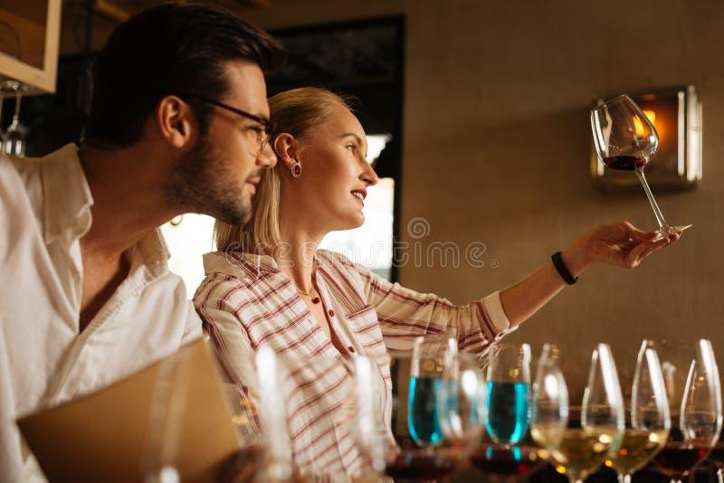 Jovem mulher agradável que tenta definir o vinho imagens de stock royalty free