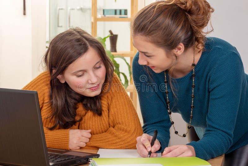 A jovem mulher ajuda uma menina adolescente com trabalhos de casa foto de stock