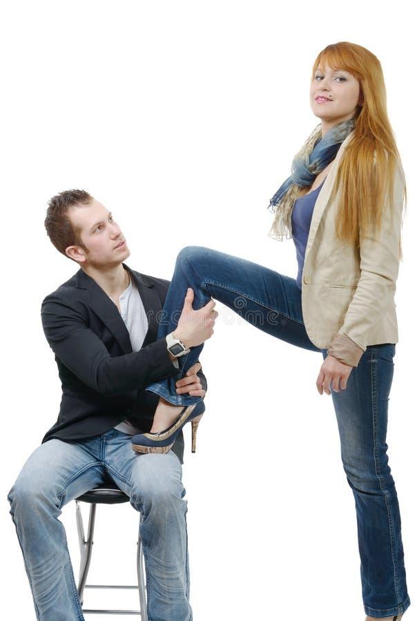A jovem mulher ajusta o pé em seu amante fotos de stock