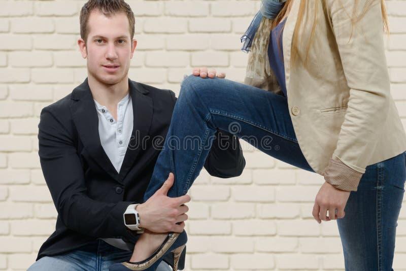 A jovem mulher ajusta o pé em seu amante imagens de stock royalty free